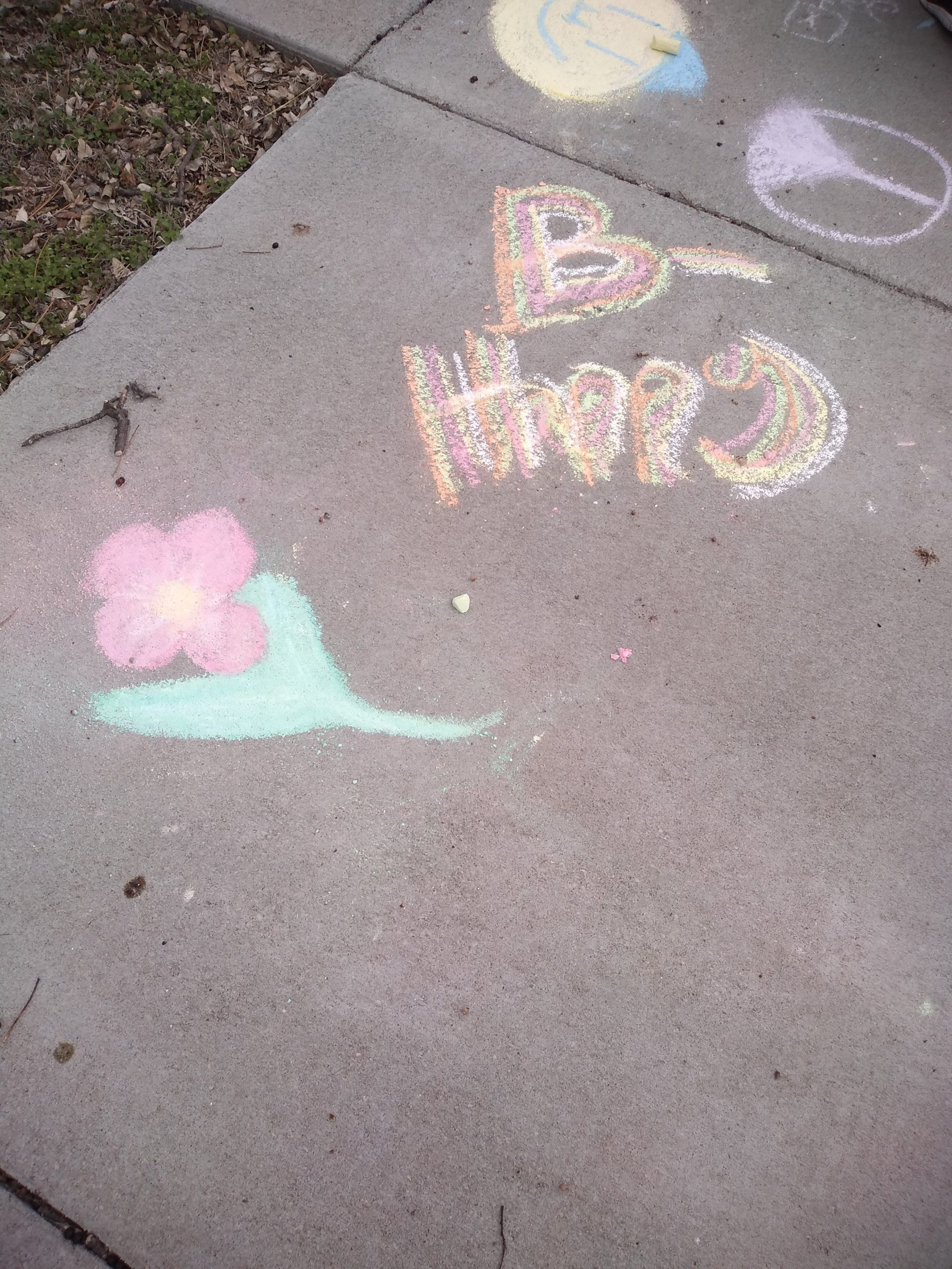 "concrete sidewalk with child's drawing of single flower and ""B-happy""."