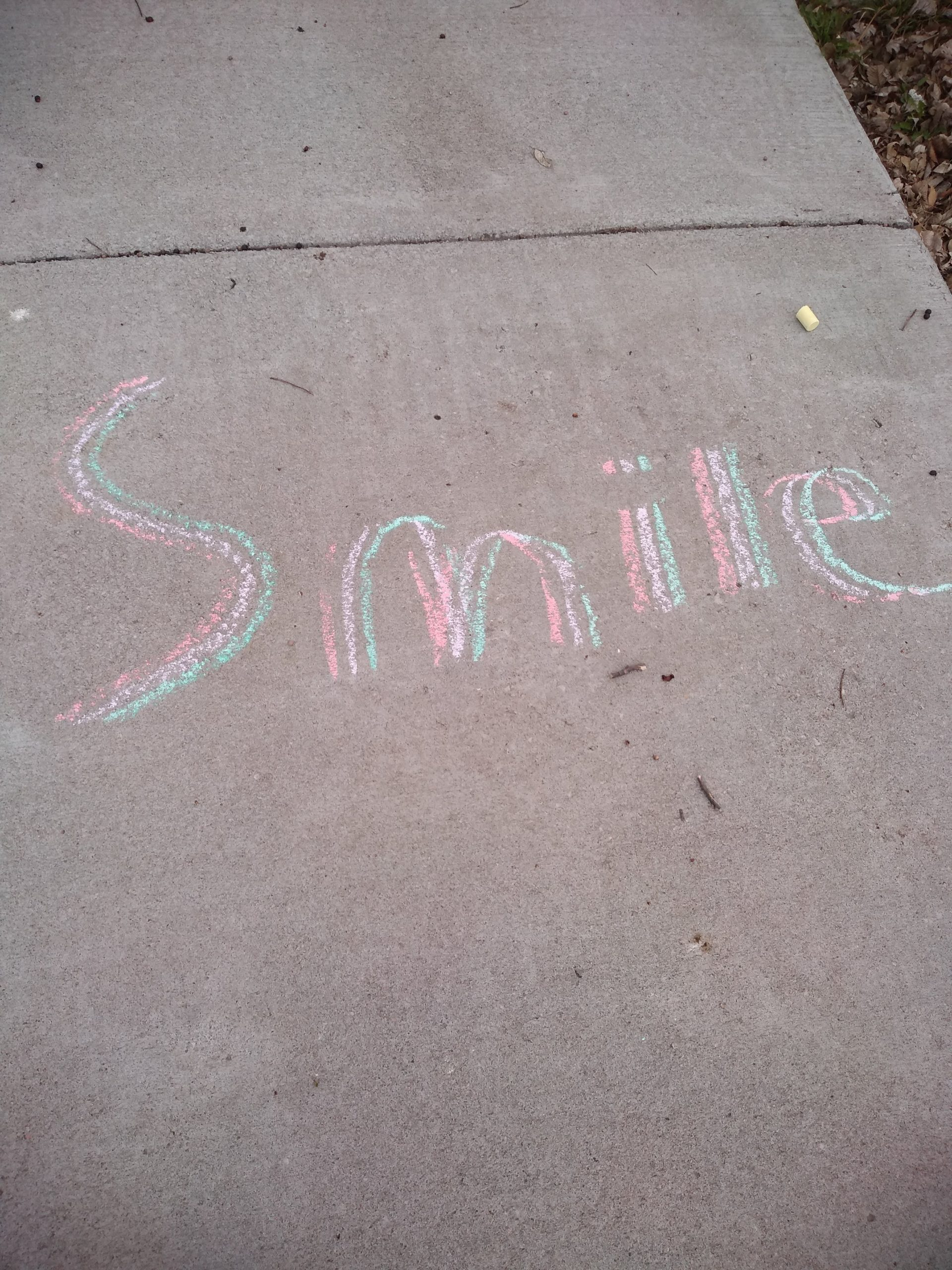 "concrete sidewalk with blue, pink, and Yellow chalk drawing the word ""smile""."