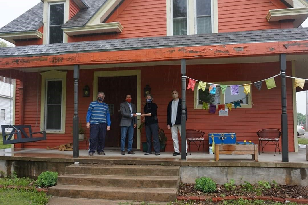 4 masked and social distanced people standing on porch of 2 story orange house, receiving a donation to help feed the neighbor to neighbor food for families program.