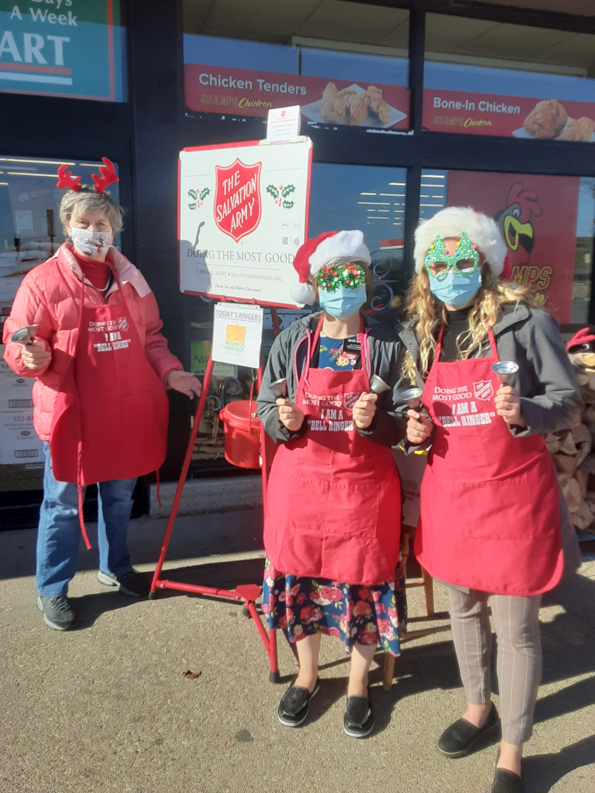 "3 ladies ringing the Salvation Army bell in front of a grocery store. the 2 teenaged girls are wearing fun, sparkly glasses with santa hats. The ""mature"" woman is wearing a headband with reindeer antlers."