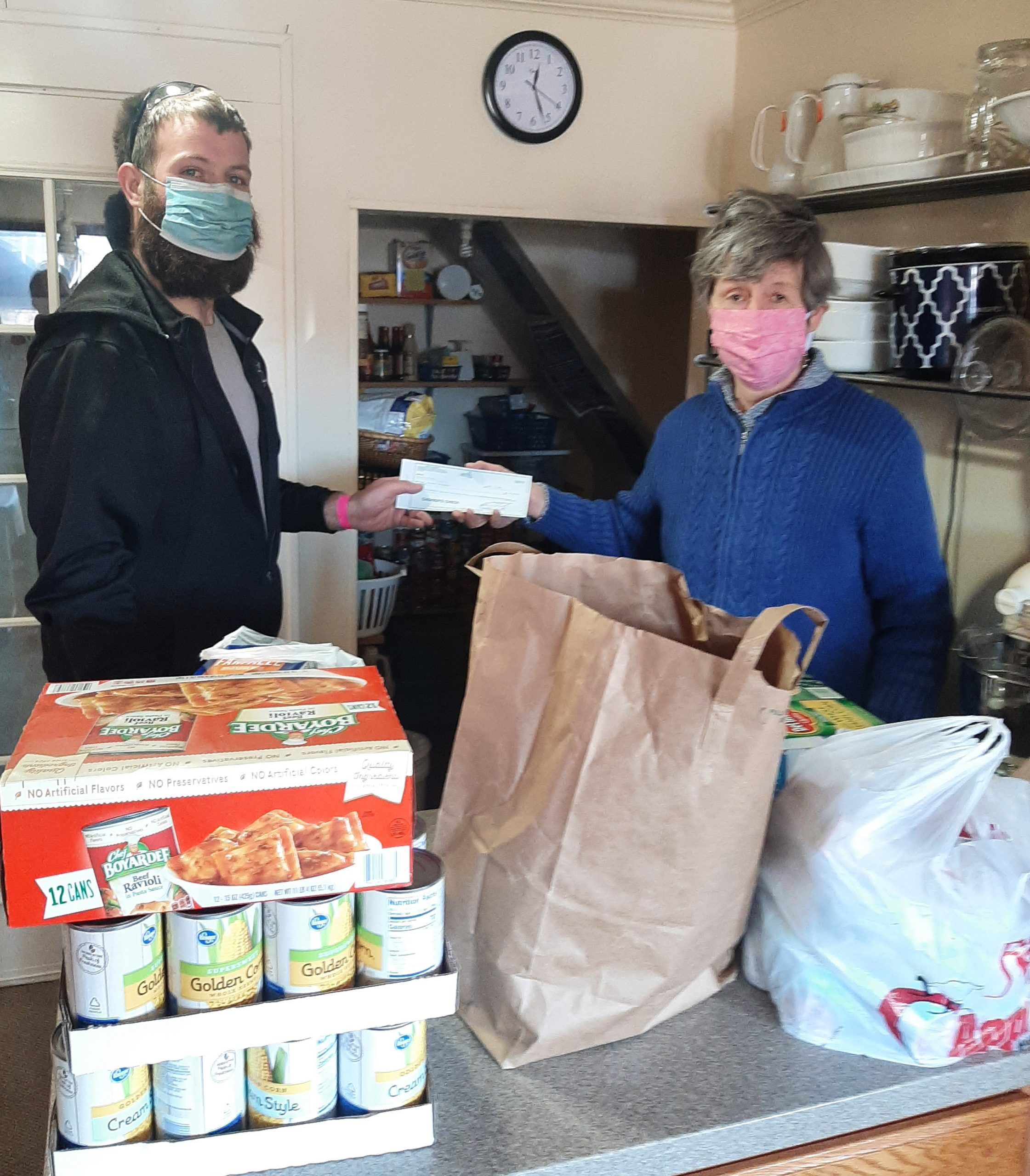 Tall man with beard and mask handing woman wearing a pink mask a check. The check was money raised during a local Frisbee tournament. Also shown are food items that were also donated along with the money.