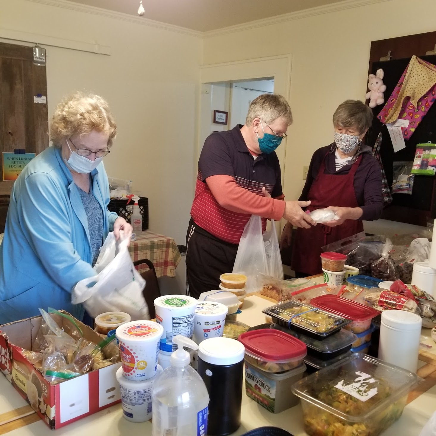 2 females and 1 male, all wearing masks and gloves packing free meals into plastic bags for disbursement to the community.