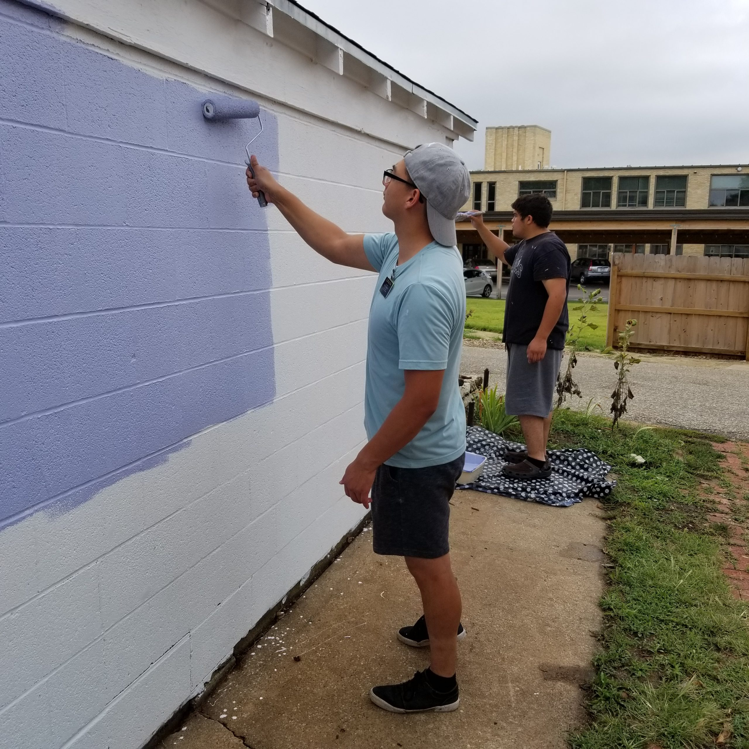 2 young adult males painting the side of a garage that will be the site of a mural.